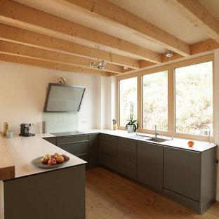 他の地域の中くらいのカントリー風おしゃれなキッチン (ドロップインシンク、フラットパネル扉のキャビネット、緑のキャビネット、青いキッチンパネル、ガラス板のキッチンパネル、無垢フローリング、茶色い床) の写真