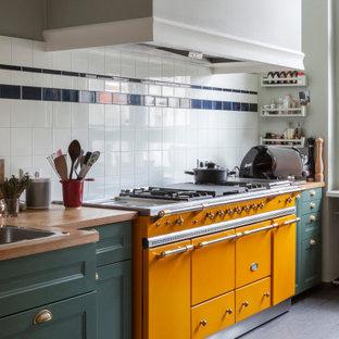 ベルリンの中くらいの地中海スタイルのおしゃれなI型キッチン (ドロップインシンク、落し込みパネル扉のキャビネット、緑のキャビネット、木材カウンター、グレーの床、茶色いキッチンカウンター) の写真