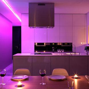 Modern inredning av ett stort kök med öppen planlösning, med släta luckor, vita skåp, rostfria vitvaror, en halv köksö och en undermonterad diskho