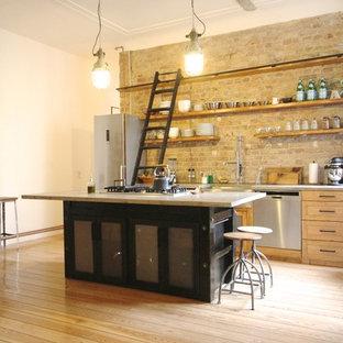 Modelo de cocina lineal, industrial, grande, abierta, con armarios con rebordes decorativos, puertas de armario de madera oscura, electrodomésticos de acero inoxidable, suelo de madera clara y una isla