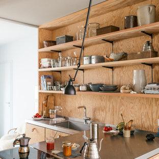 Offene, Mittelgroße Skandinavische Küche mit integriertem Waschbecken, flächenbündigen Schrankfronten, braunen Schränken, Edelstahl-Arbeitsplatte, Küchenrückwand in Braun und Küchengeräten aus Edelstahl in Berlin