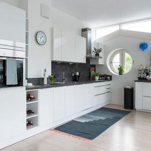 Einzeilige, Mittelgroße Moderne Küche mit flächenbündigen Schrankfronten, Küchengeräten aus Edelstahl, hellem Holzboden, weißen Schränken, Küchenrückwand in Grau, Kücheninsel und beigem Boden in Berlin