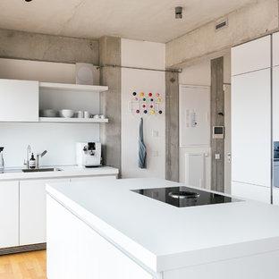 Geschlossene, Zweizeilige Industrial Küche mit Einbauwaschbecken, flächenbündigen Schrankfronten, weißen Schränken, Küchenrückwand in Weiß, schwarzen Elektrogeräten, braunem Holzboden und Kücheninsel in Berlin