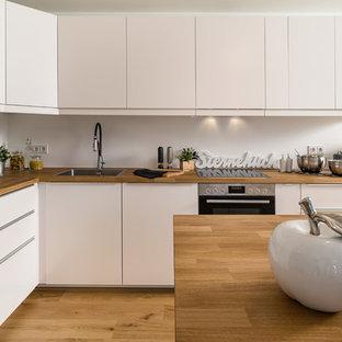 Offene, Kleine Moderne Küche in L-Form mit braunem Holzboden, braunem Boden, Einbauwaschbecken, flächenbündigen Schrankfronten, weißen Schränken, Arbeitsplatte aus Holz, Küchenrückwand in Weiß, schwarzen Elektrogeräten, Kücheninsel und brauner Arbeitsplatte in München