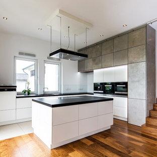 Moderne Küche in L-Form mit flächenbündigen Schrankfronten, grauen Schränken, Glasrückwand, schwarzen Elektrogeräten, braunem Holzboden, Kücheninsel, braunem Boden und schwarzer Arbeitsplatte in Hannover