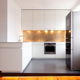 Mid-sized contemporary l-shaped separate kitchen in Munich with flat-panel cabinets, white cabinets, solid surface benchtops, metallic splashback, stainless steel appliances and linoleum floors.