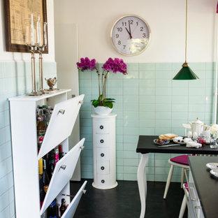 ベルリンの中サイズのエクレクティックスタイルのおしゃれなキッチン (ドロップインシンク、白いキャビネット、木材カウンター、緑のキッチンパネル、ガラスタイルのキッチンパネル、シルバーの調理設備の、リノリウムの床、黒い床、黒いキッチンカウンター) の写真