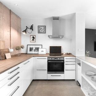 Offene, Kleine Industrial Küche in U-Form mit weißen Schränken, Arbeitsplatte aus Holz, Halbinsel, grauem Boden, brauner Arbeitsplatte, flächenbündigen Schrankfronten, schwarzen Elektrogeräten und Betonboden in Hamburg