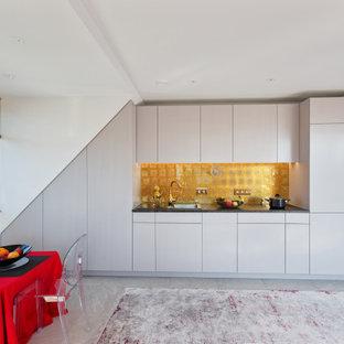Moderne Küche mit Einbauwaschbecken, flächenbündigen Schrankfronten, weißen Schränken, Küchenrückwand in Metallic, Elektrogeräten mit Frontblende, grauem Boden und schwarzer Arbeitsplatte in München