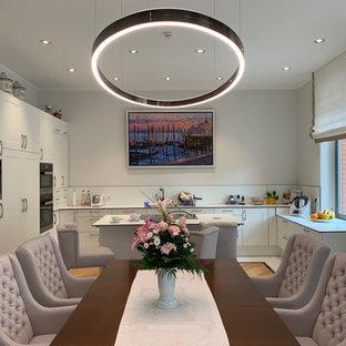Große Moderne Küche in U-Form mit Schrankfronten im Shaker-Stil, weißen Schränken, Elektrogeräten mit Frontblende, Kücheninsel und weißer Arbeitsplatte in Frankfurt am Main