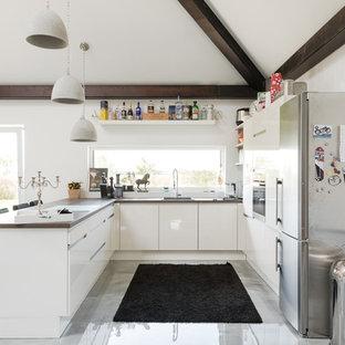 Offene, Mittelgroße Moderne Küche in U-Form mit flächenbündigen Schrankfronten, weißen Schränken, Arbeitsplatte aus Holz und schwarzen Elektrogeräten in Berlin