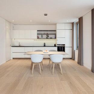Foto di una cucina moderna di medie dimensioni con lavello a vasca singola, ante lisce, ante bianche, paraspruzzi bianco, elettrodomestici neri, parquet chiaro e nessuna isola