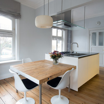 Example of a mid-sized trendy beige floor and medium tone wood floor open concept kitchen design in Hamburg with an integrated sink, flat-panel cabinets, white cabinets, an island and gray countertops