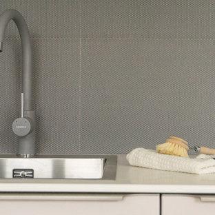 Inredning av ett modernt litet vit vitt kök, med en nedsänkt diskho, släta luckor, lila skåp, bänkskiva i koppar, grått stänkskydd, stänkskydd i stenkakel, integrerade vitvaror, mellanmörkt trägolv och brunt golv