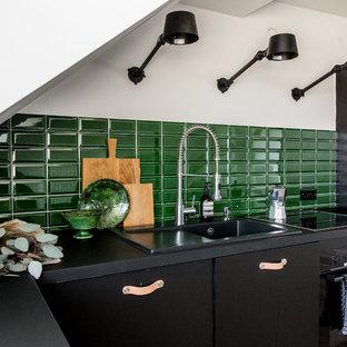 Moderne Küche in L-Form mit Einbauwaschbecken, flächenbündigen Schrankfronten, schwarzen Schränken, Küchenrückwand in Grün, Rückwand aus Metrofliesen und schwarzer Arbeitsplatte in Berlin