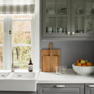 Landhausstil Küche mit Landhausspüle, profilierten Schrankfronten, grauen Schränken, Küchenrückwand in Grau und weißer Arbeitsplatte in Hamburg