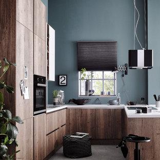 Inredning av ett industriellt litet kök, med en nedsänkt diskho, släta luckor, bruna skåp, träbänkskiva, blått stänkskydd, stänkskydd i tegel, mörkt trägolv, en halv köksö, brunt golv och svarta vitvaror