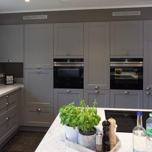 Foto di un'ampia cucina stile rurale con lavello da incasso, ante a filo, ante grigie, top in granito, paraspruzzi grigio, elettrodomestici neri, pavimento in gres porcellanato, isola, pavimento nero e top bianco