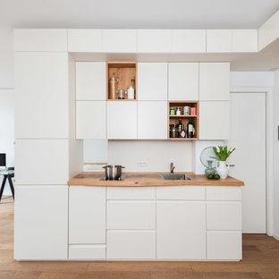 ベルリンの小さいコンテンポラリースタイルのおしゃれなキッチン (フラットパネル扉のキャビネット、白いキャビネット、木材カウンター、無垢フローリング、ドロップインシンク、白いキッチンパネル) の写真