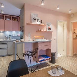 Mittelgroße Moderne Wohnküche in L-Form mit Einbauwaschbecken, flächenbündigen Schrankfronten, grauen Schränken, Küchenrückwand in Grau, braunem Holzboden, braunem Boden, Halbinsel und grauer Arbeitsplatte in Sonstige