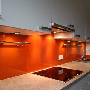 他の地域の小さいコンテンポラリースタイルのおしゃれなII型キッチン (フラットパネル扉のキャビネット、ラミネートカウンター、オレンジのキッチンパネル、ガラス板のキッチンパネル、シルバーの調理設備) の写真