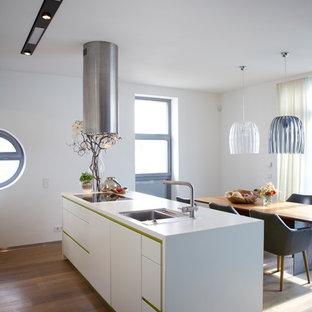 Mittelgroße Moderne Wohnküche mit Einbauwaschbecken, flächenbündigen Schrankfronten, weißen Schränken, braunem Holzboden, Kücheninsel, braunem Boden und weißer Arbeitsplatte in Köln