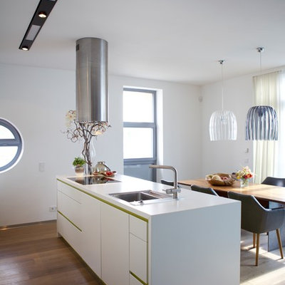 Inspiration for a mid-sized contemporary medium tone wood floor and brown floor eat-in kitchen remodel in Cologne with a drop-in sink, flat-panel cabinets, white cabinets, an island and white countertops