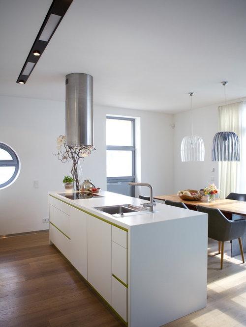 Mittelgroße Moderne Wohnküche Mit Einbauwaschbecken, Flächenbündigen  Schrankfronten, Weißen Schränken, Braunem Holzboden, Kücheninsel