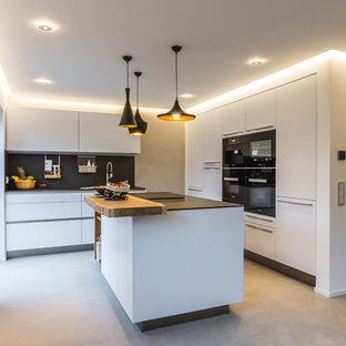 Design ideas for a mid-sized contemporary l-shaped kitchen in Frankfurt with white cabinets, black appliances, with island, a single-bowl sink, flat-panel cabinets, black splashback, concrete floors, grey floor and black benchtop.
