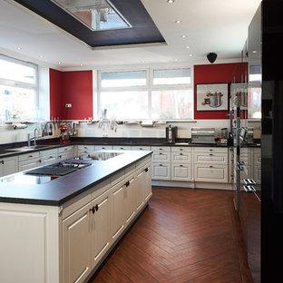 Offene, Große Country Küche in U-Form mit Einbauwaschbecken, profilierten Schrankfronten, weißen Schränken, Küchenrückwand in Weiß, Glasrückwand, schwarzen Elektrogeräten, braunem Holzboden, zwei Kücheninseln und braunem Boden in Bremen