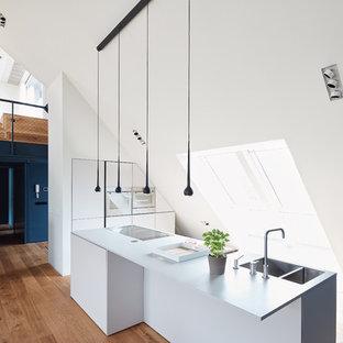 Große, Einzeilige Moderne Wohnküche mit integriertem Waschbecken, flächenbündigen Schrankfronten, weißen Schränken, braunem Holzboden, Kücheninsel, braunem Boden und Küchengeräten aus Edelstahl in Berlin