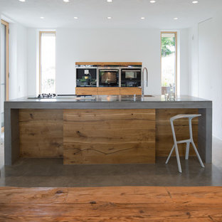 This is an example of a mid-sized contemporary open plan kitchen in Munich with an integrated sink, flat-panel cabinets, medium wood cabinets, concrete benchtops, white splashback, stainless steel appliances, concrete floors, with island, grey floor and grey benchtop.