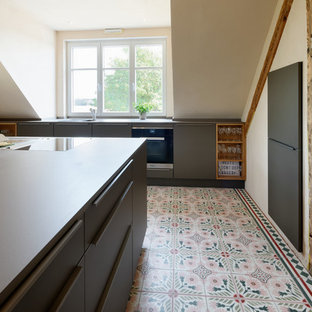 Photo of a contemporary galley open plan kitchen in Essen with a drop-in sink, flat-panel cabinets, black cabinets, black appliances, ceramic floors, with island, multi-coloured floor and black benchtop.