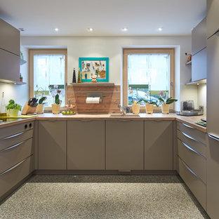 Mittelgroße Moderne Küche mit Unterbauwaschbecken, flächenbündigen Schrankfronten, grauen Schränken, Küchenrückwand in Weiß, buntem Boden und Arbeitsplatte aus Holz in München