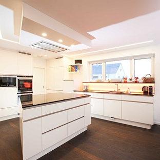 Offene, Mittelgroße Moderne Küche in L-Form mit flächenbündigen Schrankfronten, weißen Schränken, Küchenrückwand in Weiß, Glasrückwand, schwarzen Elektrogeräten, dunklem Holzboden, Kücheninsel, braunem Boden und schwarzer Arbeitsplatte in Stuttgart