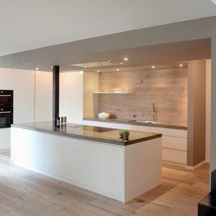 Foto de cocina moderna, grande, abierta, con fregadero de doble seno, armarios con paneles lisos, puertas de armario blancas, suelo de madera clara, una isla, salpicadero marrón y electrodomésticos negros