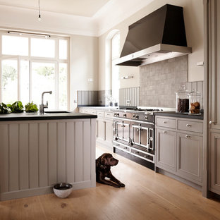 Design ideas for a large country open plan kitchen in Hamburg with an undermount sink, recessed-panel cabinets, grey cabinets, grey splashback, black appliances, light hardwood floors, with island and brown floor.