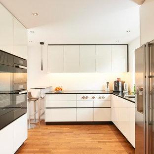 Mittelgroße Moderne Küche ohne Insel in U-Form mit flächenbündigen Schrankfronten, weißen Schränken, Küchenrückwand in Weiß, schwarzen Elektrogeräten, braunem Holzboden, braunem Boden, Unterbauwaschbecken und schwarzer Arbeitsplatte in Stuttgart