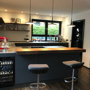 Design ideas for a large industrial u-shaped kitchen/diner in Other with an integrated sink, flat-panel cabinets, grey cabinets, engineered stone countertops, white splashback, brick splashback, stainless steel appliances, dark hardwood flooring, a breakfast bar and yellow worktops.
