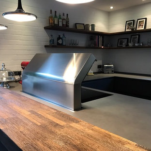This is an example of a large industrial u-shaped eat-in kitchen in Other with an integrated sink, flat-panel cabinets, grey cabinets, quartz benchtops, white splashback, brick splashback, stainless steel appliances, dark hardwood floors, a peninsula and yellow benchtop.