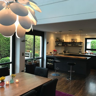 Photo of a large urban u-shaped kitchen/diner in Other with an integrated sink, flat-panel cabinets, grey cabinets, engineered stone countertops, white splashback, brick splashback, stainless steel appliances, dark hardwood flooring, a breakfast bar and yellow worktops.