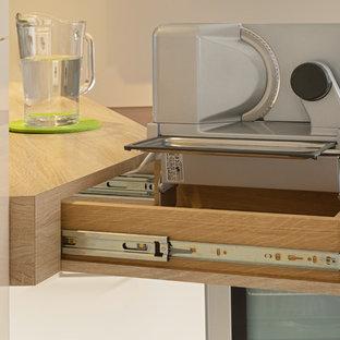 ミュンヘンの小さいコンテンポラリースタイルのおしゃれなキッチン (一体型シンク、フラットパネル扉のキャビネット、白いキャビネット、珪岩カウンター、白いキッチンパネル、ガラス板のキッチンパネル、シルバーの調理設備の、磁器タイルの床、白い床、茶色いキッチンカウンター) の写真