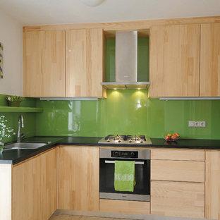シュトゥットガルトの大きいコンテンポラリースタイルのおしゃれなキッチン (ドロップインシンク、フラットパネル扉のキャビネット、淡色木目調キャビネット、御影石カウンター、緑のキッチンパネル、ガラス板のキッチンパネル、シルバーの調理設備の、淡色無垢フローリング、アイランドなし) の写真