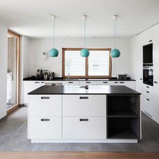 Offene, Große Moderne Küche in L-Form mit Waschbecken, flächenbündigen Schrankfronten, weißen Schränken, Granit-Arbeitsplatte, Küchenrückwand in Weiß, Küchengeräten aus Edelstahl, Keramikboden, grauem Boden und zwei Kücheninseln in München