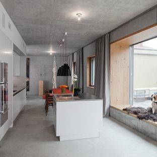 Esempio di una cucina minimal di medie dimensioni con ante lisce, ante bianche, top in acciaio inossidabile, elettrodomestici in acciaio inossidabile e isola