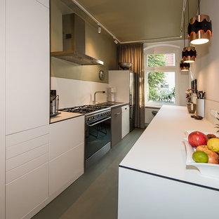 Idee per una piccola cucina parallela minimal chiusa con lavello da incasso, ante lisce, ante bianche, top in laminato, paraspruzzi bianco, elettrodomestici in acciaio inossidabile, pavimento in linoleum, nessuna isola, pavimento verde e top bianco