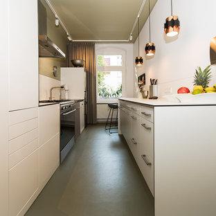 Cette photo montre une petite cuisine parallèle tendance fermée avec un évier posé, un placard à porte plane, des portes de placard blanches, un plan de travail en stratifié, une crédence blanche, un électroménager en acier inoxydable, un sol en linoléum, aucun îlot, un sol vert et un plan de travail blanc.
