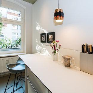Diseño de cocina de galera, contemporánea, pequeña, cerrada, sin isla, con fregadero encastrado, armarios con paneles lisos, puertas de armario blancas, encimera de laminado, salpicadero blanco, electrodomésticos de acero inoxidable, suelo de linóleo, suelo verde y encimeras blancas