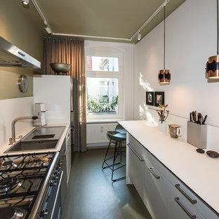 Réalisation d'une petite cuisine parallèle design fermée avec un évier posé, un placard à porte plane, des portes de placard blanches, un plan de travail en stratifié, une crédence blanche, un électroménager en acier inoxydable, un sol en linoléum, aucun îlot, un sol vert et un plan de travail blanc.