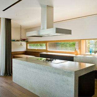 ミュンヘンの中サイズのコンテンポラリースタイルのおしゃれなキッチン (一体型シンク、フラットパネル扉のキャビネット、黒いキャビネット、木材カウンター、ガラス板のキッチンパネル、無垢フローリング) の写真